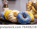 donuts in icing and other fillings in the pastry shop 76408238