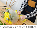 Florist makes a bouquet of fresh yellow tulips. 76410071