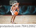 Young athletic man in white sportwear playing basket-ball in the gym 76412662