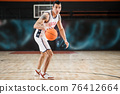 Young athletic man in white sportwear playing basket-ball in the gym 76412664