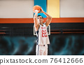 Dark-haired athletic man playing basket-ball in the gym 76412666