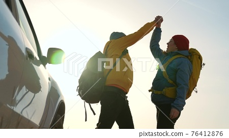 teamwork success. car a travelers with backpacks silhouette win. victory teamwork business freedom concept. friendly team of hikers silhouette. business success. happy family on a car with backpacks 76412876
