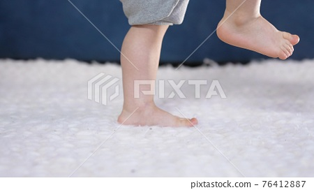 feet baby a learns to indoor walk. first steps of a newborn close-up at home. baby feet kicking learns to walk. A cute boy learns to walk and take his first steps. concept newborn close-up 76412887