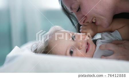 baby son. mom a kissing baby son on the bed. mom and baby love and care concept happy family. Mom kissing cute boy. newborn and mother indoor parent close-up on the bed concept care 76412888