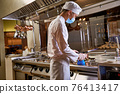 Cook using gas torch on a kitchen 76413417