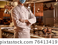 Proud chef standing with crossed arms in kitchen 76413419