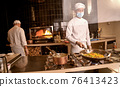 Asian cook keeping peppers in pan over stove burner 76413423