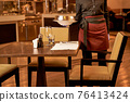 Person lowering a covered dish on a table with cutlery 76413424