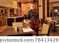 Female server bringing a dish under a steel lid 76413426