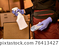 Hands of waitress with folded cleaning rag and spray 76413427