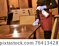 Female restaurant worker rubbing a table with cloth 76413428