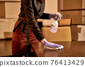 Waiter tidying a table with spray detergent 76413429