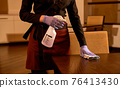 Waitress is cleaning table with disinfectant spray 76413430