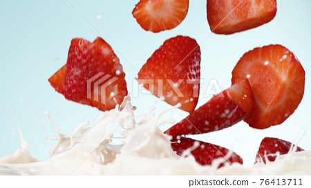 Strawberries falling into milk 76413711