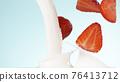 Strawberries falling into milk 76413712