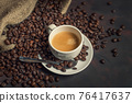 Coffee espresso teaspoon and roasted beans on dark background 76417637