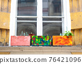 colorful flowerpots on a house window 76421096
