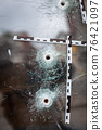 bullet holes in a glass shop window marked with a police tape 76421097