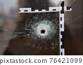 bullet holes in a glass shop window marked with a police tape 76421099