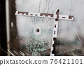 bullet holes in a glass shop window marked with a police tape 76421101