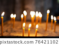 burning candles during a ceremony in a church 76421102