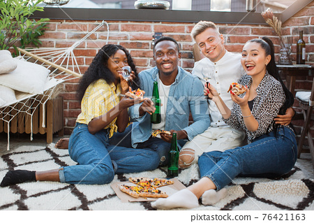 Four friends enjoying pizza and alcoholic drinks on party 76421163