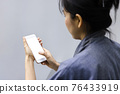 A woman shopping online on her sofa at home with a smartphone using and tap the screen to verify the identity. Concept about business. over shoulder shot. 76433919