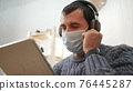 telework. man in a medical mask works remotely in a digital tablet wearing a medical protective freelance mask. office home telework concept. man in a medical protective mask works at home 76445287