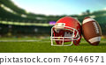American football ball and helmet on the grass of football arena or stadium. 76446571