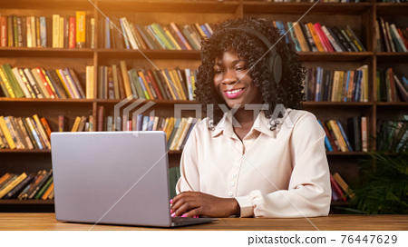 African-American woman has videocall from home library 76447629