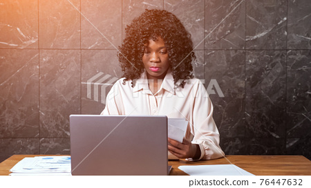 Black businesswoman gathers papers and types on laptop 76447632