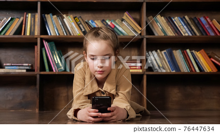 Junior student in brown jacket plays game on smartphone 76447634