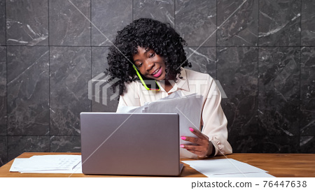 Woman manager explains via smartphone and looks at papers 76447638