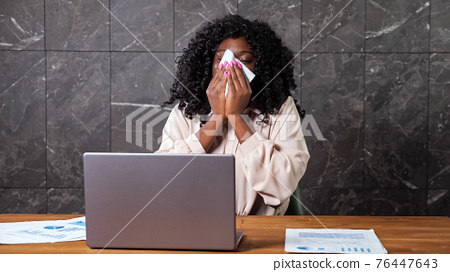 Tired Afro-american worker lady sneezes into paper napkin 76447643