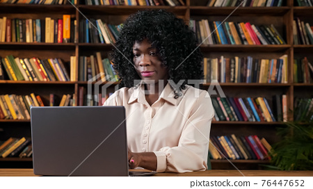 African-Amarican businesswoman works on laptop at table 76447652