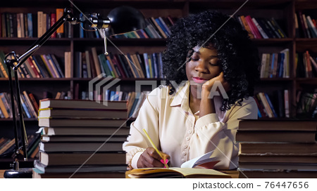 African-American woman writes at table in semi-dark room 76447656