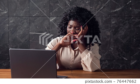 Black businesswoman with curly hair types on laptop lazily 76447662
