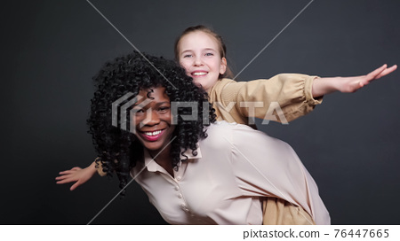 Stylish black stepmother holds adopted schoolgirl on backs 76447665