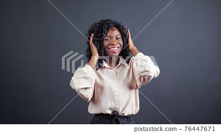 African-American lady with headphones dances on black 76447671