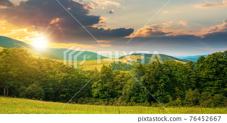 summer landscape of carpathian mountains at sunset. beautiful scenery in evening light. beech forest and grassy alpine meadows on the hills. clouds on the dramatic sky 76452667