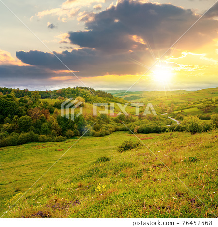 carpathian countryside in spring at sunset. beautiful rural landscape in mountain. wet grassy meadow in evening light. road winding through valley to village. distant ridge in the clouds 76452668