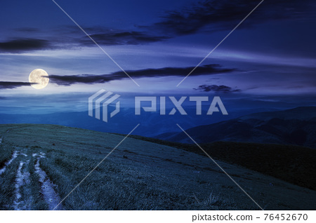 country road through alpine meadow at night. beautiful nature landscape in summer. scenery with open view in to the distant ridge and valley in full moon light. sky with clouds above the horizon 76452670