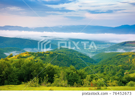 mountainous rural landscape at sunrise. trees and agricultural fields on hills rolling in to the distant valley full of fog. ridge beneath a sky with clouds in morning light 76452673