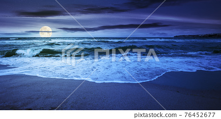 sea tide on a cloudy sunrise. green waves crashing golden sandy beach in full moon light. storm weather approaching. summer holiday concept 76452677