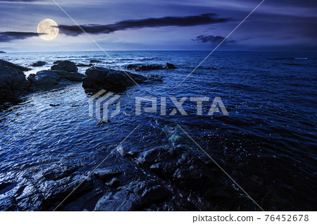 sea coast scenery at night. boulders in the calm water. few clouds on the sky in full moon light. lonely place for summer vacations. sunny weather 76452678