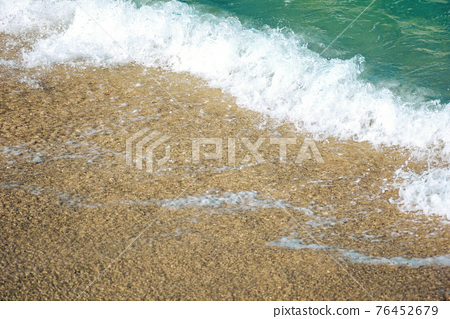 close up texture of the sea wave rolling on to the golden sandy beach. abstract nature background on a sunny summer day 76452679