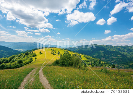 road through meadow in mountains. beautiful rural landscape of carpathians on a sunny day. wonderful summer weather with fluffy clouds on the sky 76452681