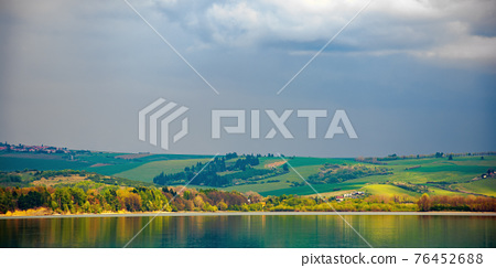 liptovska mara lake of slovakia. beautiful landscape in spring. reflection on the water surface. distant mountains in clouds 76452688