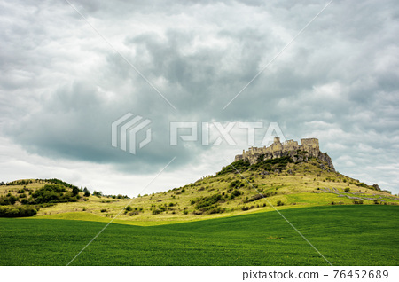 spis, slovakia - 29 APR 2019: castle ruins on the hill. grassy meadow in the foreground. popular travel destination on a cloudy day 76452689