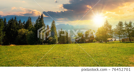rural landscape in tatra mountains at sunset. spruce trees on the green grassy meadow of gubalowka range. beautiful nature scenery in evening light. clouds above the distant ridge 76452701